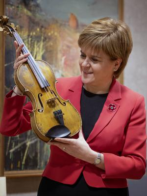First Minister Nicola Sturgeon takes a closer look at the Wilfred Owen violin (Jane Barlow/PA)