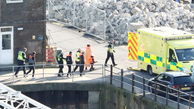 Migrants are led to an ambulance as they are brought ashore in Dover (Gareth Fuller/PA)