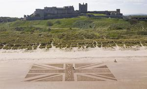 A giant Union flag was drawn in the sand on the beach beneath Bamburgh Castle in Northumberland by maintenance manager Andrew Heeley, 56 (Owen Humphreys/PA)