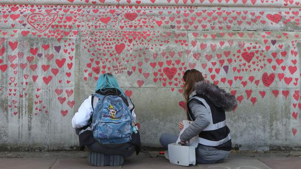 Volunteers add hearts to the National Covid Memorial Wall in Westminster, central London (Luciana Guerra/PA)