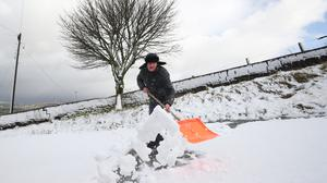 A man clears snow at the Waggon and Horses Inn, Oxenhope (Danny Lawson/PA)