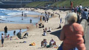 People enjoy the hot weather at Whitley Bay beach in Tyneside as people flock to parks and beaches with lockdown measures eased (PA)