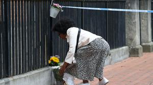 A woman places flowers at the Abbey gateway of Forbury Gardens (Jonathan Brady/PA)