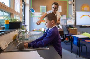 Reception pupil Braydon washes his hands whilst watching an electronic timer (Joe Giddens/PA)
