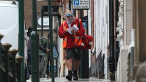 A postman delivers mail in Oldham, Greater Manchester (Peter Byrne/PA)