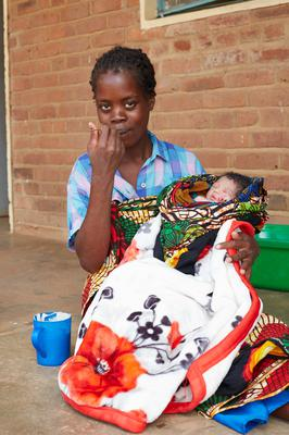 Lucia, 26, mother to newborn baby Bertha, eating a special porridge made from soya, maize flour and sugar which is given to mums after childbirth in Malawi (WaterAid/Jenny Lewis/PA)