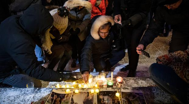 Mourners place candles and photographs outside the Alberta Legislature Building in Edmonton, Alberta, Wednesday, Jan. 8, 2020, during a vigil for those killed after a Ukrainian passenger jet crashed, killing at least 63 Canadians, just minutes after taking off from Iran's capital (Codie McLachlan/The Canadian Press/AP)