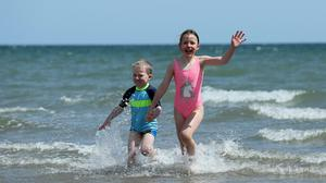 Four year old Cian Walshe, four, and his sister Ella, eight, play in the sea off Portmarnock Beach, Dublin, as the warm weather continues (Brian Lawless/PA Wire)