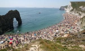 People enjoying the good weather on the beach at Durdle Door, near Lulworth in Dorset, at the end of May as lockdown was relaxed (Andrew Matthews/PA)