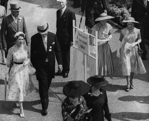 The Queen (left) and Princess Margaret (far right) walk to the paddock at the postponed Royal Ascot race meeting in July 1955 (PA)