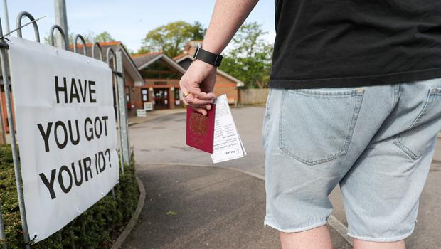 A voter carries his passport along with his poll card in Knaphill, Woking (Andrew Matthews/PA)