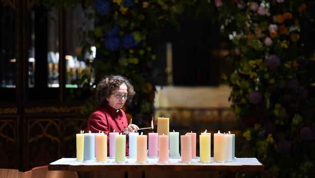 A member of the clergy lights candles for the victims during the Manchester Arena National Service of Commemoration at Manchester Cathedral (Paul Ellis/PA)