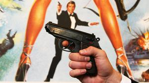 A Walther PPK handgun in front of a poster of the film 'For Your Eyes Only' at Christie's in London before the auction of a variety of weapons from James Bond films.