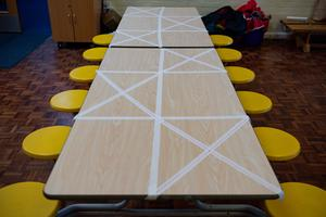 Tables are marked showing where children can sit during dinner time at a primary School in Worcester (Jacob King/PA)
