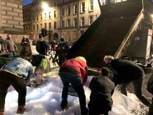 A truck dumped ice at the corner of George Square and was transported to the main pile by buckets, bags and jackets (Douglas Barrie/PA)
