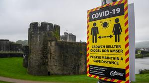 "Covid-19 signage opposite Caerphilly castle advises on social distancing as the county borough in south Wales is to be placed under a local lockdown following a ""significant rise"" in coronavirus cases. People will not be allowed to enter or leave the area without a reasonable excuse when the restrictions come into force from 6pm on Tuesday, the Welsh Government said."