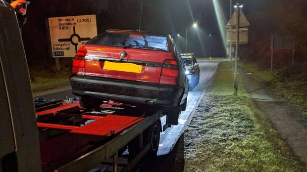 The car was hanging off the side of the truck when it was stopped in West Lothian (Police Scotland/PA)