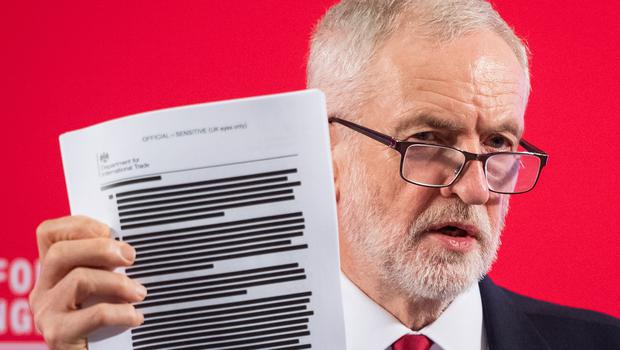 Labour leader Jeremy Corbyn holds a redacted copy of the Department for International Trade's UK-US Trade and Investment Working Group report (Dominic Lipinski/PA)