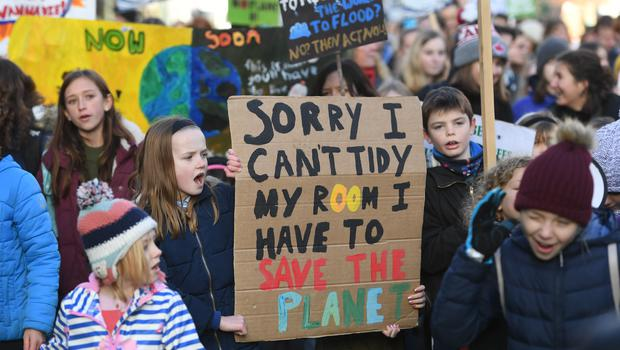 Young protesters hold up banners during the march in Cambridge (Joe Giddens/PA)