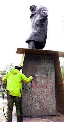 A worker with a high-pressure water gun blasts paint off the statue a day after the demonstration (John Stillwell/PA)