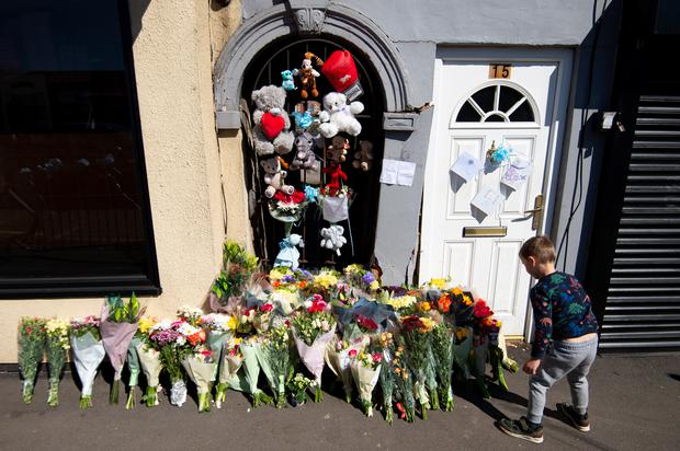 A boy lays flowers at the scene (Jacob King/PA)