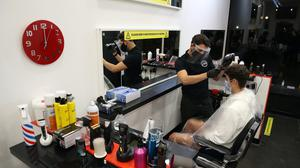 First customer Mitchell Wildman in the chair at Tony Mann's Barber Shop in Giffnock (Andrew Milligan/PA)