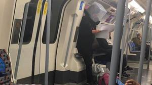 A woman with a box on her head on the London Underground (Sabina Ana)