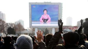 North Koreans watch a news broadcast on a video screen outside Pyongyang Railway Station (AP)