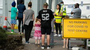 Members of the public speak with staff while queuing at a coronavirus testing facility at the University of Birmingham (Jacob King/PA)