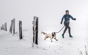 A woman runs with a dog through a snow covered scene near Buxton in Derbyshire last week (Danny Lawson/ PA)