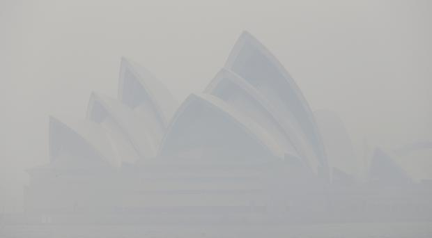Thick smoke from wildfires shrouds the Sydney Opera House (Rick Rycroft/AP)