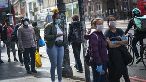 People wearing protective face masks wait in line for a supermarket in Brixton, south London (Victoria Jones/PA)