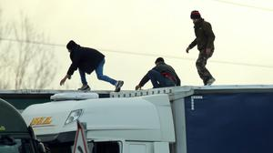Migrants on the roof of a lorry as it moves along the A16 in Calais (PA)