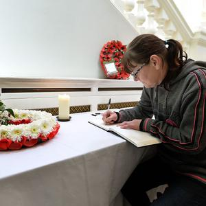 Caroline McNiffe writes a message in a book of condolence to Drummer Lee Rigby in Woolwich Town Hall, south east London