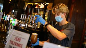 Bar staff in PPE pour drinks at the reopening a Wetherspoon pub