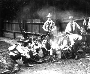 A group of Boy Scouts sitting around a camp fire in 1910 (PA)