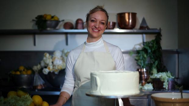 Claire Ptak, owner of Violet Bakery in Hackney, east London, with a tier of the cake for the wedding of Prince Harry and Meghan Markle in the kitchens at Buckingham Palace (Hannah McKay/PA)