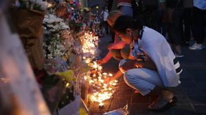 People look at flowers and tributes outside Notting Hill Methodist Church (Yui Mok/PA)