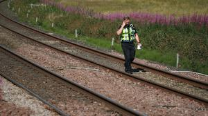 A police officer walks along the tracks at Carmont crossing, south of the scene in Stonehaven (Jane Barlow/PA