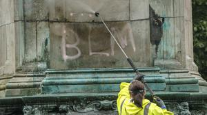 Council workers clean graffiti, that included the letters 'BLM' and the words 'murderer' and 'slave owner', from a statue of Queen Victoria in Woodhouse Moor, Leeds (PA)