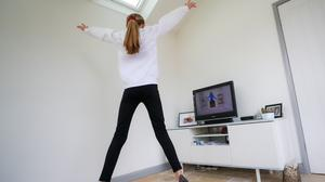 """A 12-year-old girl from Derbyshire takes part in """"PE with Joe"""", a daily live workout with Joe Wicks streamed on Youtube to help kids stay fit while staying indoors following the Corona virus outbreak (Scott Wilson/PA)."""