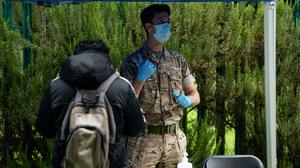 A member of the military instructs a person taking a test at a Covid-19 testing centre in Spinney Hill Park in Leicester (Jacob King/PA)