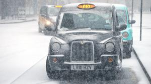 Taxis in the snow in London (Jonathan Brady/PA)