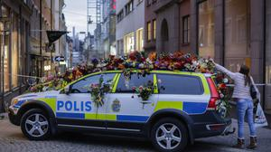 A woman drops flowers on to a police car near the department store where the attack took place (AP)