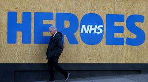 A person walks past a boarded-up shop in Glasgow with an NHS tribute (Andrew Milligan/PA)
