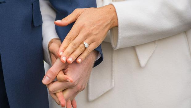 Prince Harry and Meghan Markle, wearing her engagement ring, hold hands at their engagement photocall (Dominic Lipinski/PA)