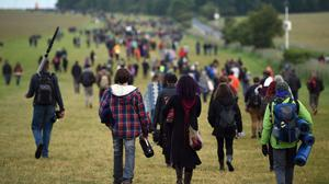 Memebers fo the public make their way back to the car park at Stonehenge in Wiltshire after seeing in the new dawn