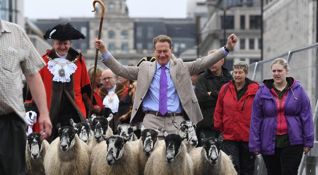 Michael Portillo leads a flock of sheep over London Bridge (Kirsty O'Connor/PA)