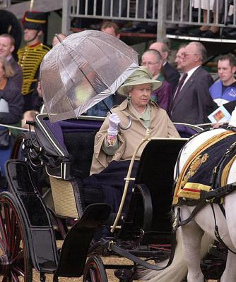 The Queen with an umbrella and a waterproof coat during a rainy carriage procession to Trooping in 2001 (Michael Stephens/PA)