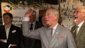 The Prince of Wales plays darts during a visit to the Fleece Inn (Aaron Chown/PA)